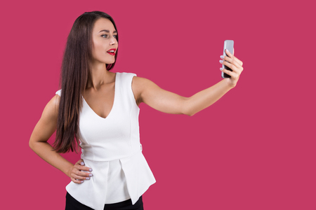 narcissistic: Narcissistic business lady with muscular hands is taking a selfie and looking pleased with herself. Mock up