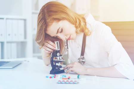 new medicine: Portrait of woman doctor in lab looking at bacteria through microscope. Concept of pharmaceutical research and new medicine invention Stock Photo