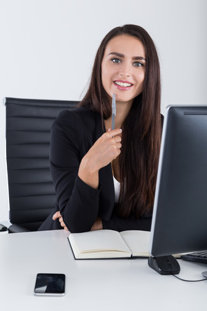 looking at viewer: Gorgeous business lady in black is interested  in converstion with you. She is looking at the viewer with spark in the eyes. Concept of interesting conversation Stock Photo