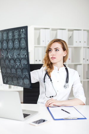 diagnose: Gorgeous woman doctor with red hair is looking at x ray image trying to diagnose her patient. Concept of difficult case Stock Photo