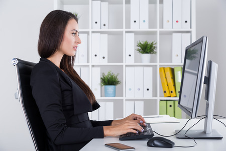 Side view of woman in black in office. She is working at her personal computer and does not want to chat with colleagues off camera. Concept of good employee