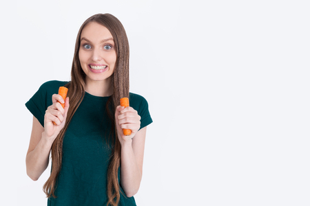 maniacal: Maniacal girl in green T-shirt is holding carrot halves and looking to camera with man eyes. Concept of no meat no mental health. Mock up