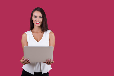 looking at viewer: Smiling businesswoman with long dark hair is holding a gray laptop in her hands. She is looking at the viewer and hypnotising them. Mock up Stock Photo