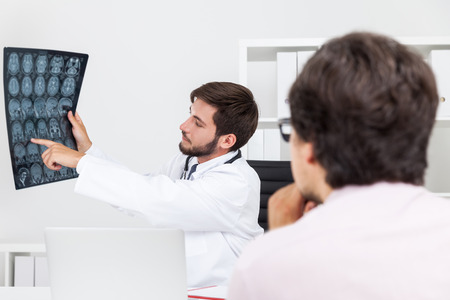 x ray image: Bearded doctor is explaining to his patient what is wrong with him and showing x ray image. Concept of details explanation