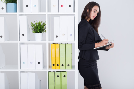 Pretty businesswoman with long dark hair is writing down her notes in large book. Concept of business planning and time management Stock Photo