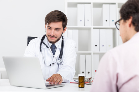 prescribing: Smiling doctor with beard is telling to his patient that he is cured and free to leave the hospital. Concept of pilling medical bills. Stock Photo