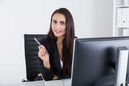 looking at viewer: Mysterious business lady is sitting in her armchair and looking at the viewer with numb question in her eyes. Concept of good manager Stock Photo