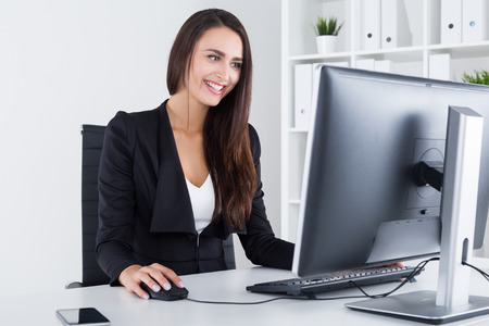 importance: Smiling businesswoman looking at desktop screen and browsing the net. Concept of good break importance