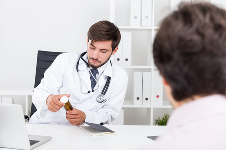 prescribing: Bearded doctor is pleased with new drug pharmacy company employee is showing him. Concept of new way to treat diseases.