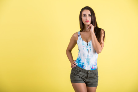 about you: Pensive girl in shorts and tank top standing with her hand near face against yellow background. Concept of thinking about you. Mock up