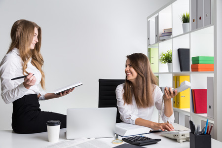 socialization: Two young businesswomen talking and enjoying socialization at workplace. Concept of good relations importance in work team. Stock Photo