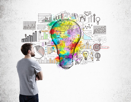 t bulb: Side view of man in T-shirt examining startup sketch on concrete wall with colorful light bulb icon in center. Concept of small business Stock Photo