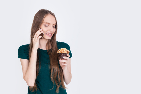Girl in green T-shirt with smartphone looking at tasty cupcake with foretaste. Concept of yummy snack. Mock up