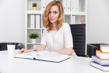 reading material: Business lady with large book. Pile of reading material in corner. Two leather armchairs and shelves with binders in background. Concept of making a research. Stock Photo
