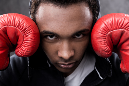 boxing match: Serious African American boxer standing with hands near face frowning. Concept of boxing match