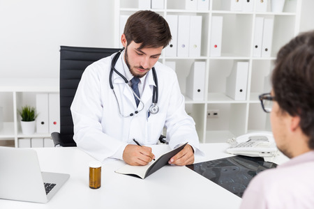 Bearded doctor is writing in his notebook while listening to his patient talk. Concept of importance of small details in medical work