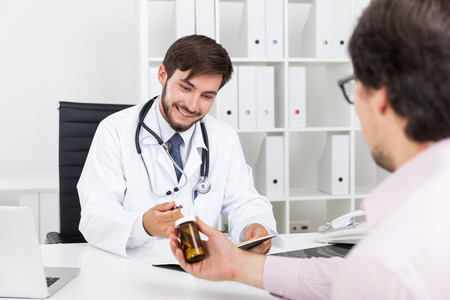 commercialism: Smiling doctor looking at jar of pills and listening to tales from pharmacy company employee trying to sell him new experimental drugs. Concept of commercialism in medicine
