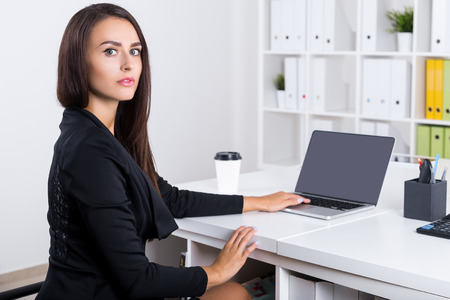 looking at viewer: Alert business woman looking at the viewer while sitting at her workplace and touching laptop keyboard with one hand. Concept of busy employee