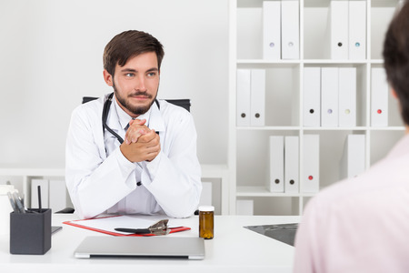 general practice: Doctor looking at his patient and rubbing his hands. They sit in doctor�s white office. Concept of disease finally cured Stock Photo