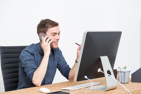 buen trato: Negocios usando su teléfono y mirando a la pantalla del ordenador sonriendo. Concepto de buen trato.