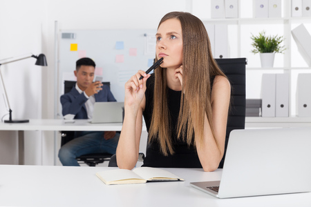 Pondering business lady in elegant black dress is thinking about new concept while her Asian colleague is stalking her from office corner. Stock Photo