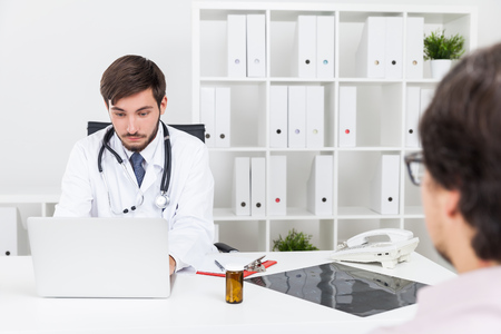 prescribing: Doctor with beard is checking details in hospital computer system. Concept of digital world advantages in medicine Stock Photo