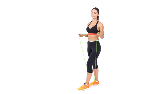 staying fit: Girl in sportswear with bright green jumping rope. Concept of staying fit and active while you can. Mock up. Stock Photo