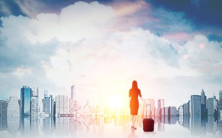 Woman with suitcase in front of  magnificent city panorama at dawn. Concept of business prospects and international company job. Toned image.