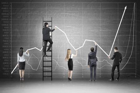 firms: Rear view of business team standing against blackboard with graphs on it drawing. Concept of everyones contribution to firms success.