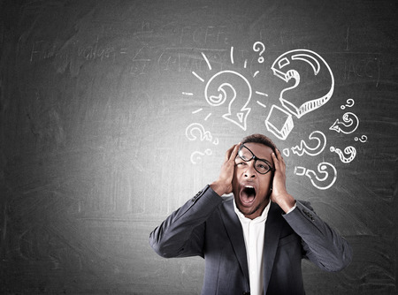 lopsided: Overwhelmed African American businessman crying near chalkboard with question mark sketches. Concept of stress and not holding up. Mock up
