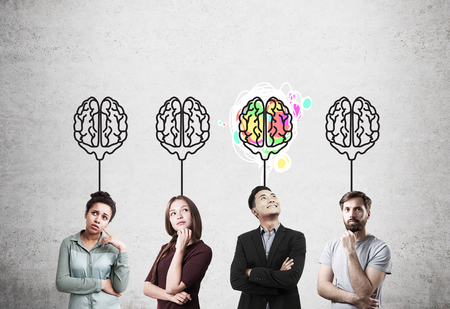 business mind: Girl in red dress, African American girl, guy in T-shirt and Asian man standing near concrete wall with brain sketches. Concept of teamwork.