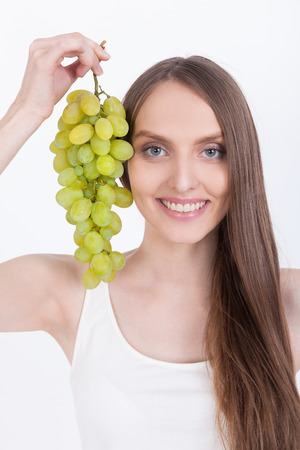 Smiling girl in white tank top holding grapes near her face and smiling broadly to the viewer. Concept of home brew vine.