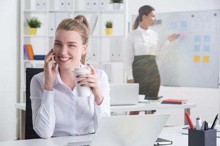 amigas conversando: Señora alegre del asunto es que tiene una conversación agradable en el lugar de trabajo durante la pausa para el café. Su colega está ensayando su discurso de presentación. Concepto de la adicción al trabajo Foto de archivo