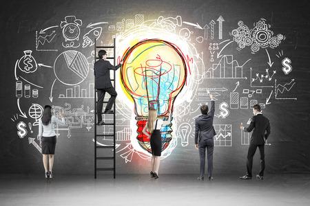 カラフルな電球とそれに描かれたスタートアップ スケッチ黒板近く事業チームの後姿。ビジネスのアイデアの概念