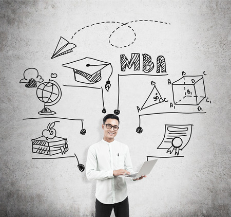 alumni: Asian man with laptop standing near concrete wall with MBA sketch. Concept of business education Stock Photo