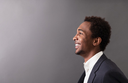 african business: Portrait of happy African American businessman in suit standing against gradient gray background and smiling broadly. Concept of success and luck in business