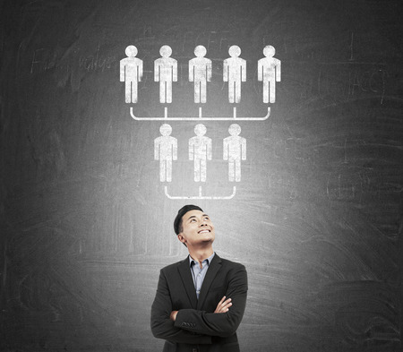 upside down: Asian businessman standing near blackboard with upside down pyramid. Concept of MLM Stock Photo