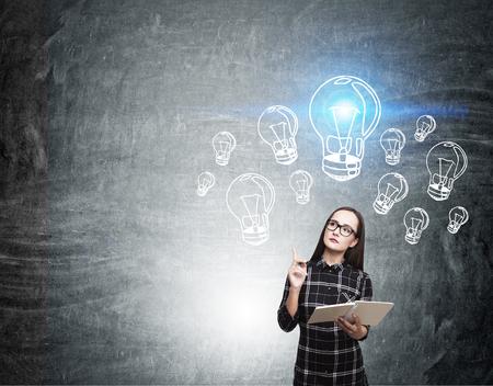 nerd girl: Nerd girl in dress standing near blackboard with blue light bulb sketches on it. Concept of great idea. Mock up