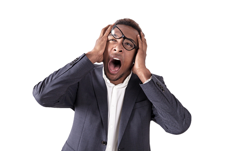 lopsided: Isolated portrait of stressed African American businessman. His glasses are lopsided. He is holding his head with both hands and screaming. Concept of overworking