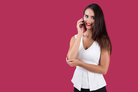 Smiling girl in white top is talking on her smartphone and looking at the viewer. Concept of communication. Mock up. Stock Photo