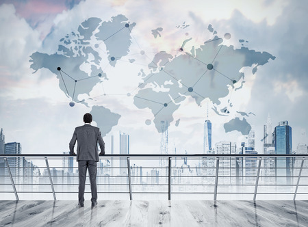 hallucinations: African American businessman is standing on his office balcony and looking at large world map in the sky. Concept of hallucinations and international trade Stock Photo