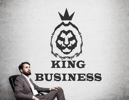 Portrait of man in brown suit sitting in his armchair near concrete wall with king of business sketch drawn on it. Concept of successful manager.
