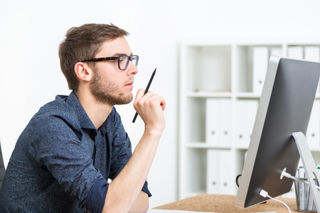Man with glasses holding pencil and looking at computer screen. Concept of problem solving