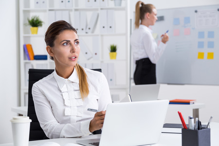 one on one meeting: One business lady is thinking about her speech during board meeting, her colleague is making notes at whiteboard preparing the presentation. Concept of important meeting
