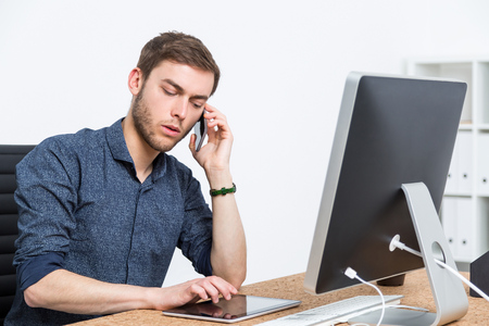 solicitor: Young businessman talking on his mobile phone sitting at office and touching tablet screen. Concept of busy day in office.