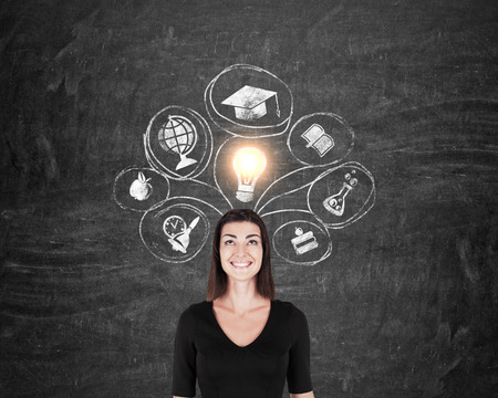 Smiling lady in black standing against blackboard with shining light bulb and education sketches. Concept of choosing your career. Mock up
