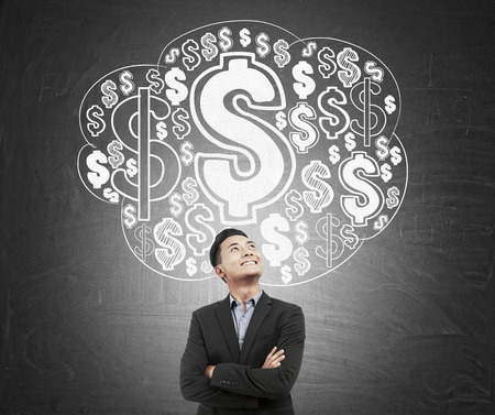 banco dinero: Asian man in black suit standing against chalkboard with dollar sign cloud. Concept of financial market Foto de archivo