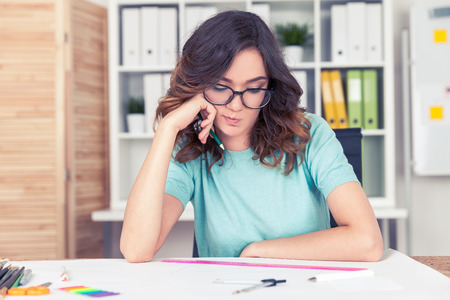 alright: Bored woman engineer wearing glasses is observing her blueprint critically trying to find a mistake. Concept of checking if everything is alright Stock Photo