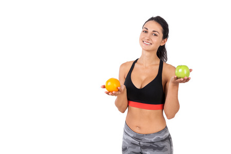 what to eat: Portrait of slim girl in sportswear choosing what to eat first: an apple or an orange. Concept of healthy food. Mock up Stock Photo