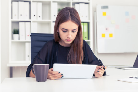 personal digital assistant: Concentrated girl in black is looking at her tablet computer screen. A cup of coffee is standing on the table beside her. Concept of business planning